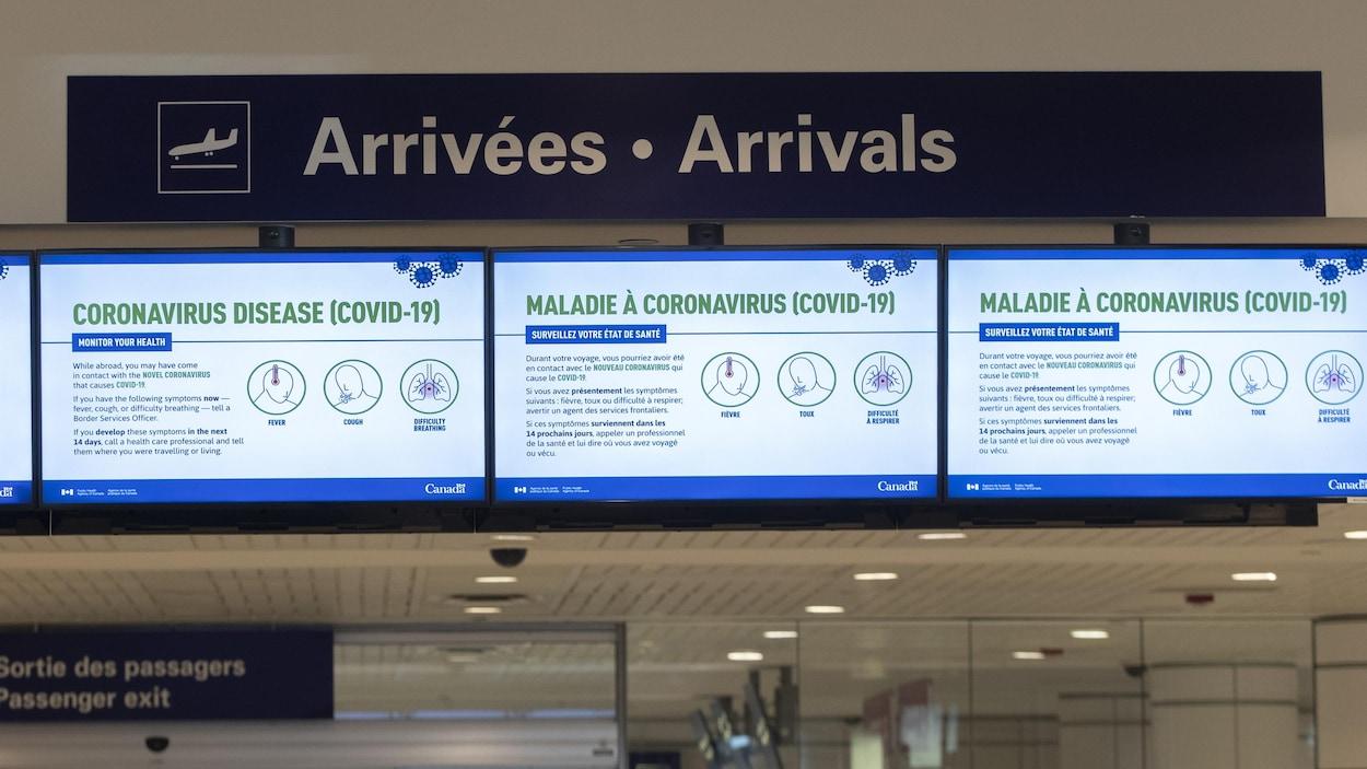 Des messages en lien avec la pandémie de la COVID-19 diffusés sur des écrans à l'aéroport de Montréal.