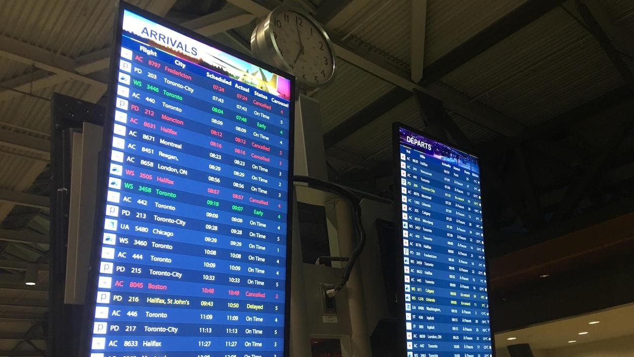 Deux panneaux (des départs et des arrivées) indiquent les annulations et les retards de vols à l'aéroport d'Ottawa.