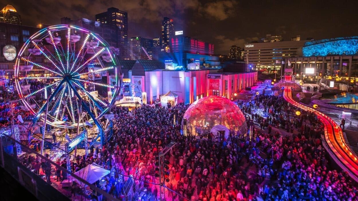 Une grande roue et une structure d'igloo sont entourées de centaines de personnes réunies au centre-ville de Montréal, illuminé, la nuit.