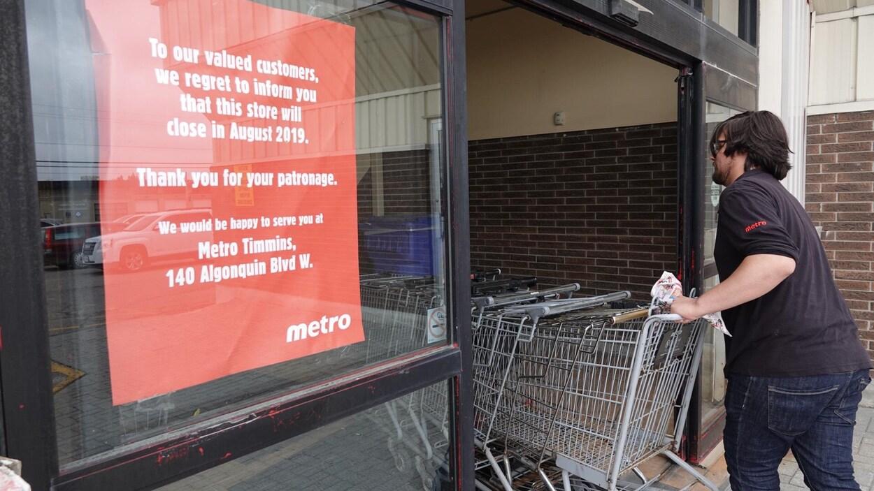 Un homme poussant des chariots d'épicerie à l'intérieur d'une épicerie.