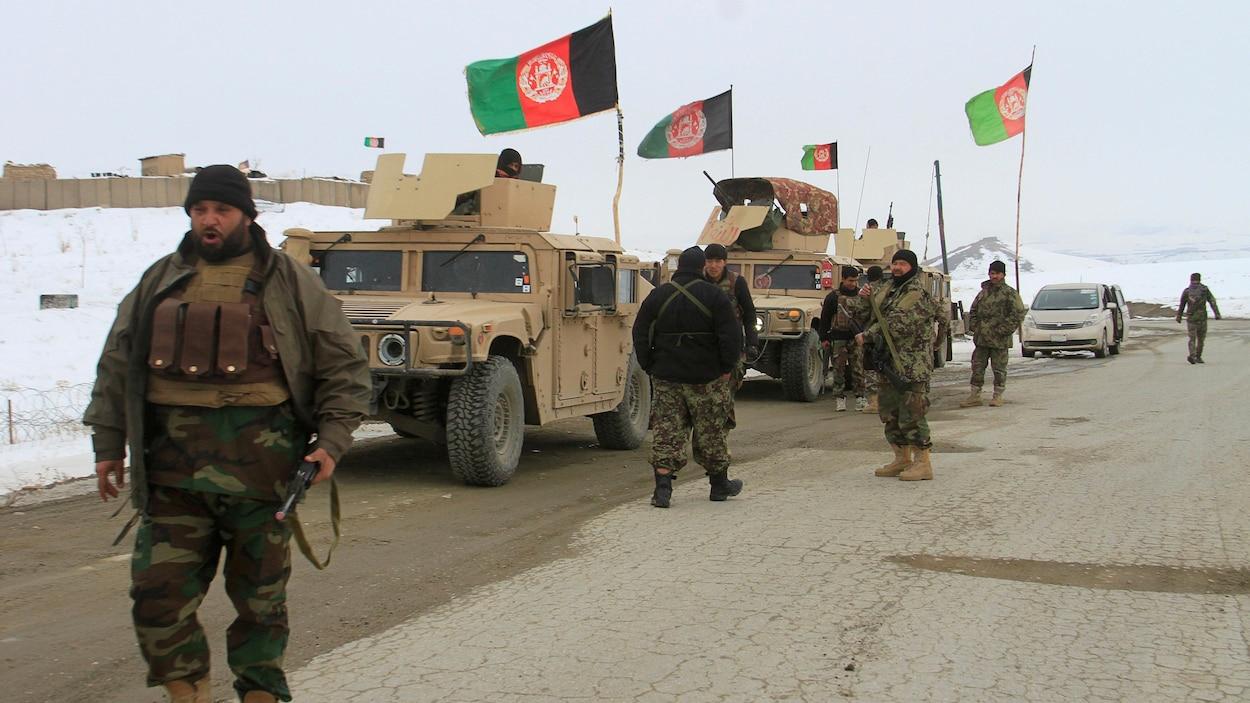 Des hommes armés en treillis militaires marchent à côté de véhicules blindés surmontés de drapeaux afghans.