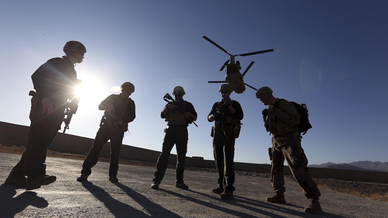 Cinq soldats américains attendent sur le tarmac pendant qu'un hélicoptère survole les lieux.