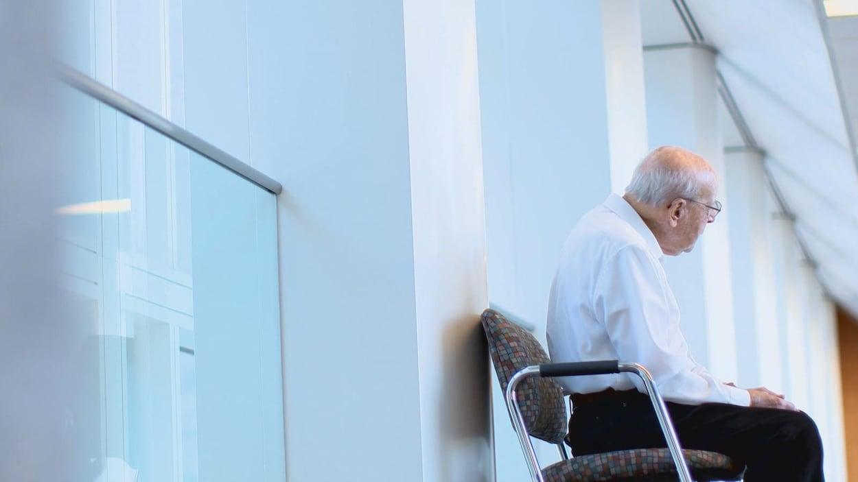 Un homme âgé assis sur une chaise dans un corridor d'hôpital.