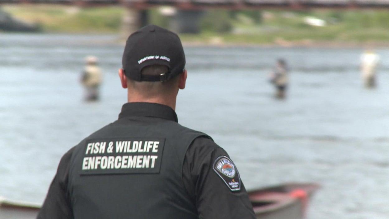 Un agent de pêche, vu de dos, regarde des pêcheurs dans une rivière.