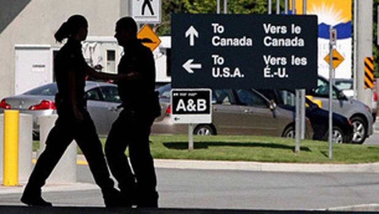 Deux agents de l'Agence des services frontaliers se croisent à l'extérieur.