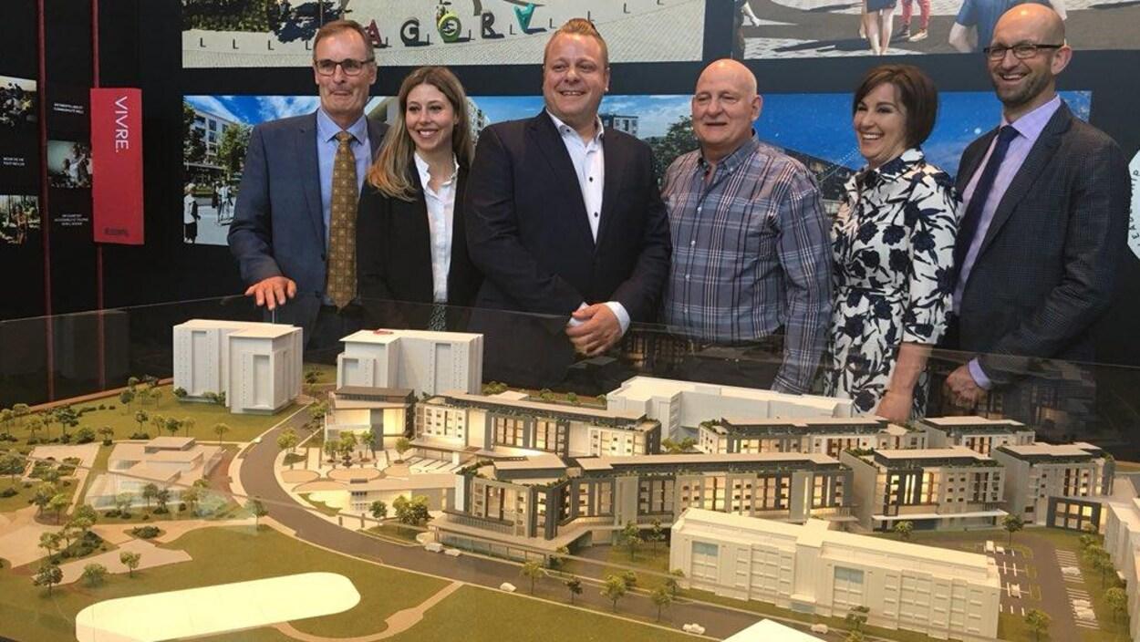 Un groupe devant une maquette d'un grand projet immobilier.