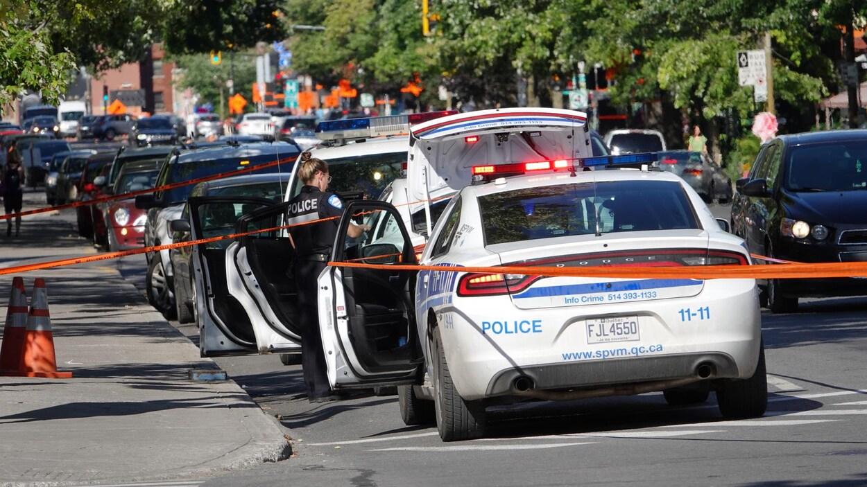 L'arrière d'une voiture de police avec le coffre ouvert et des rubans de sécurité.