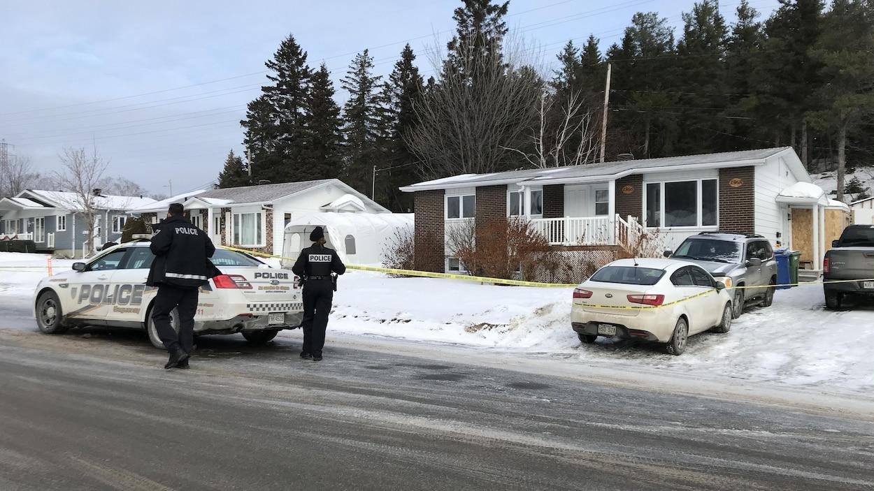 Des policiers se trouvent à l'extérieur d'un périmètre de sécurité érigé près d'une résidence.