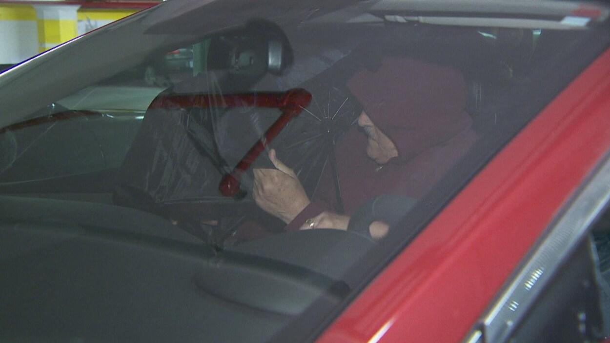 On voit Claude Trachy qui entre dans sa voiture pour échapper à la vigilance des médias en sortant du tribunal.