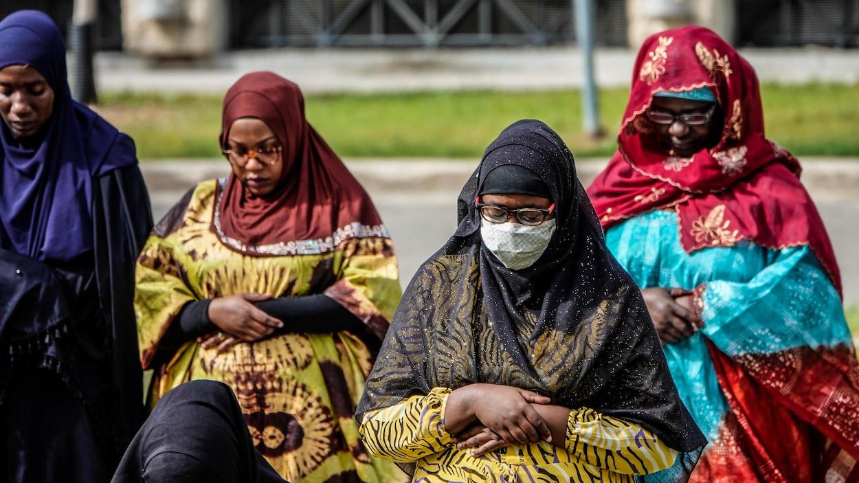 Des femmes voilées en train de prier avec l'une d'elles portant un masque.