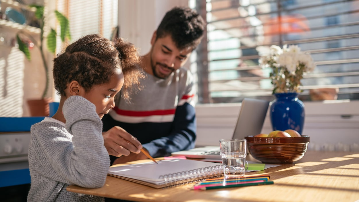Un père aide sa fille avec ses devoirs
