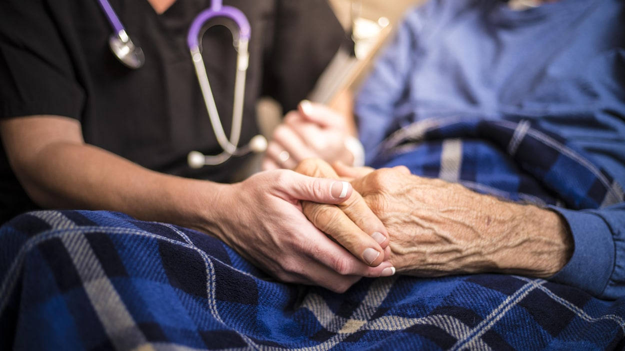Une médecin au chevet d'un patient âgé.