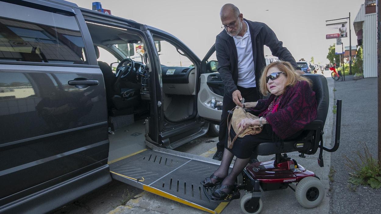 Mme Gladu sort d'un véhicule adapté pour handicapés.