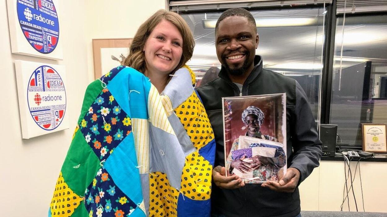 Un homme et une femme debout dans un bureau tenant une photo et une couette.