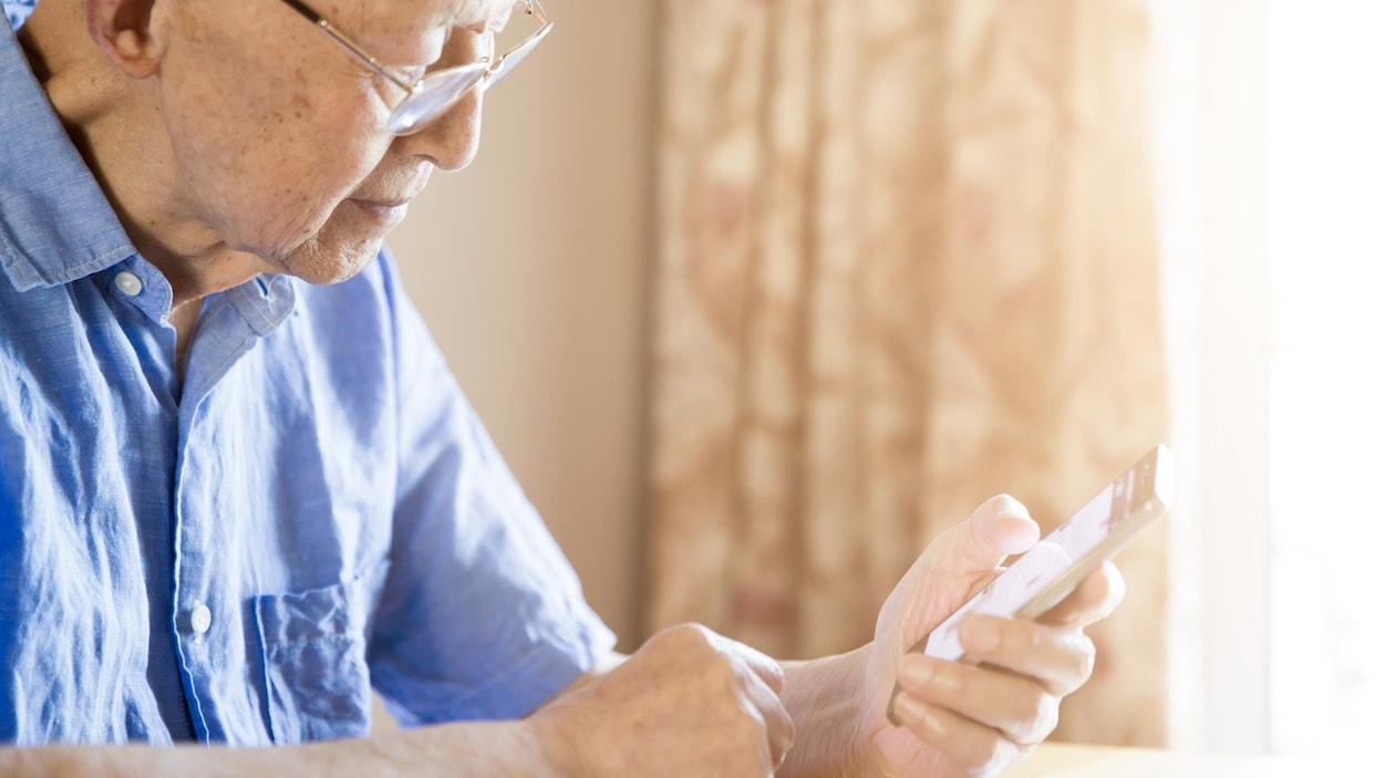 Un homme âgé utilise un cellulaire.