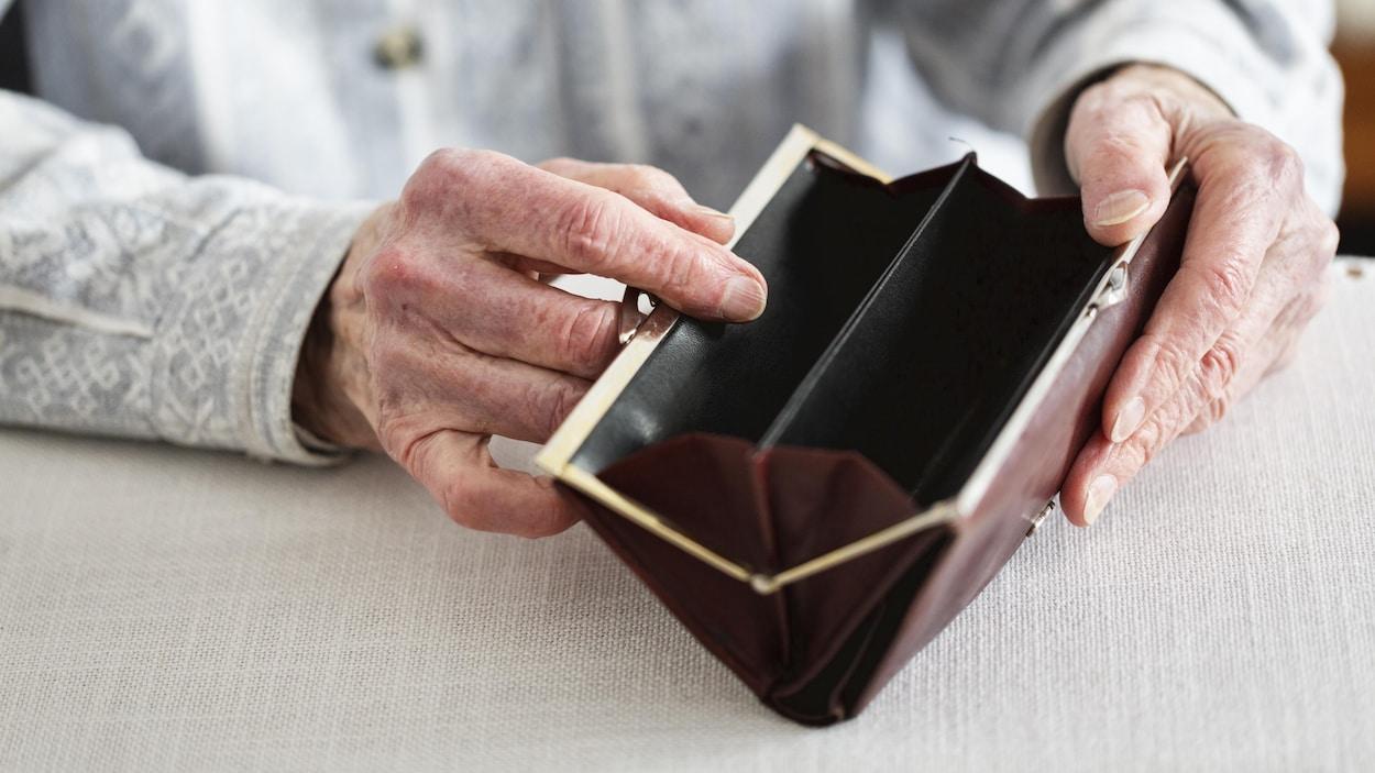 Une personne âgée tient une porte-feuille vide.