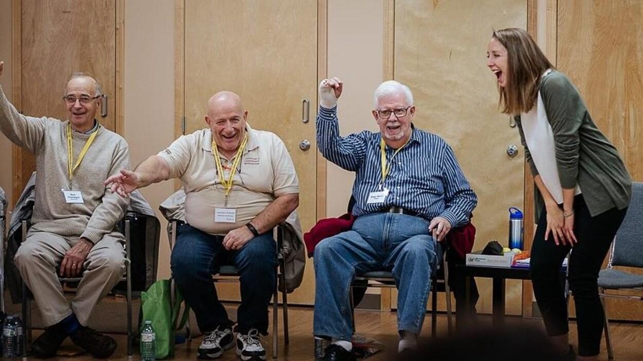 Maude Bombardier qui sourit à pleines dents avec trois aînés assis sur des chaises qui rient également.