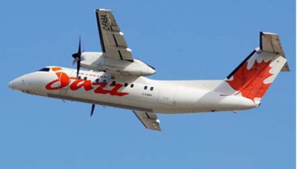 Un avion à deux hélices Dash 8-300 d'Air Canada vole sous un ciel bleu.