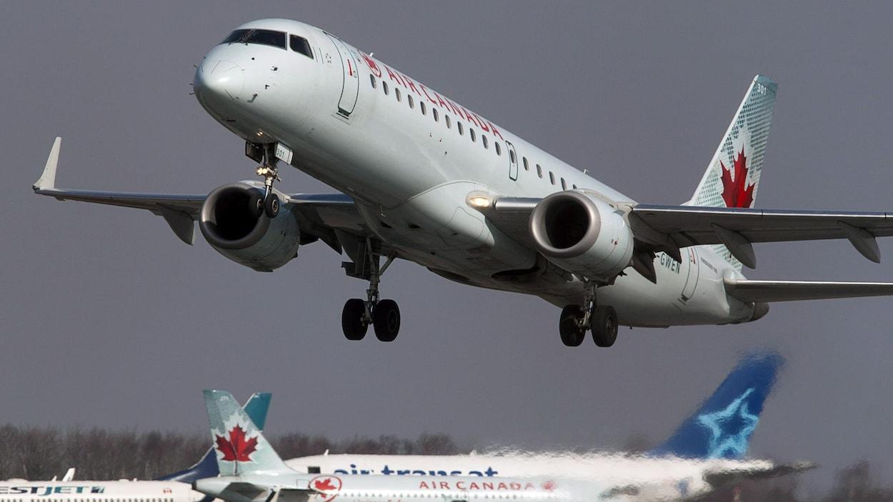 Un avion d'Air Canada décolle près d'autres appareils.