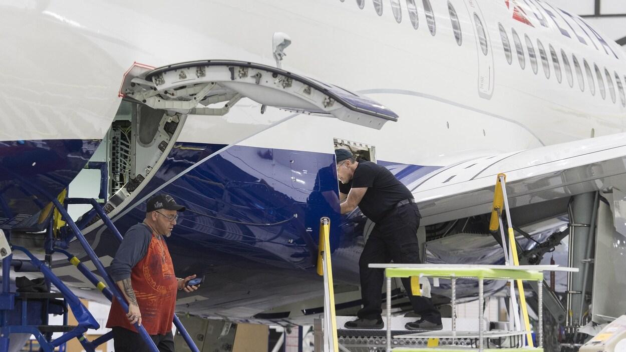 Des employés travaillent sur un avion