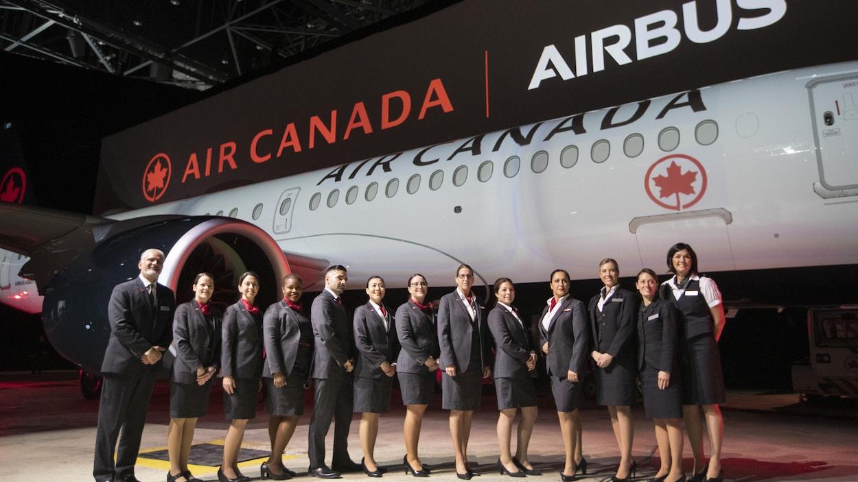 Des employés d'Air Canada posent devant un avion A220-300 dans un hangar à Montréal.