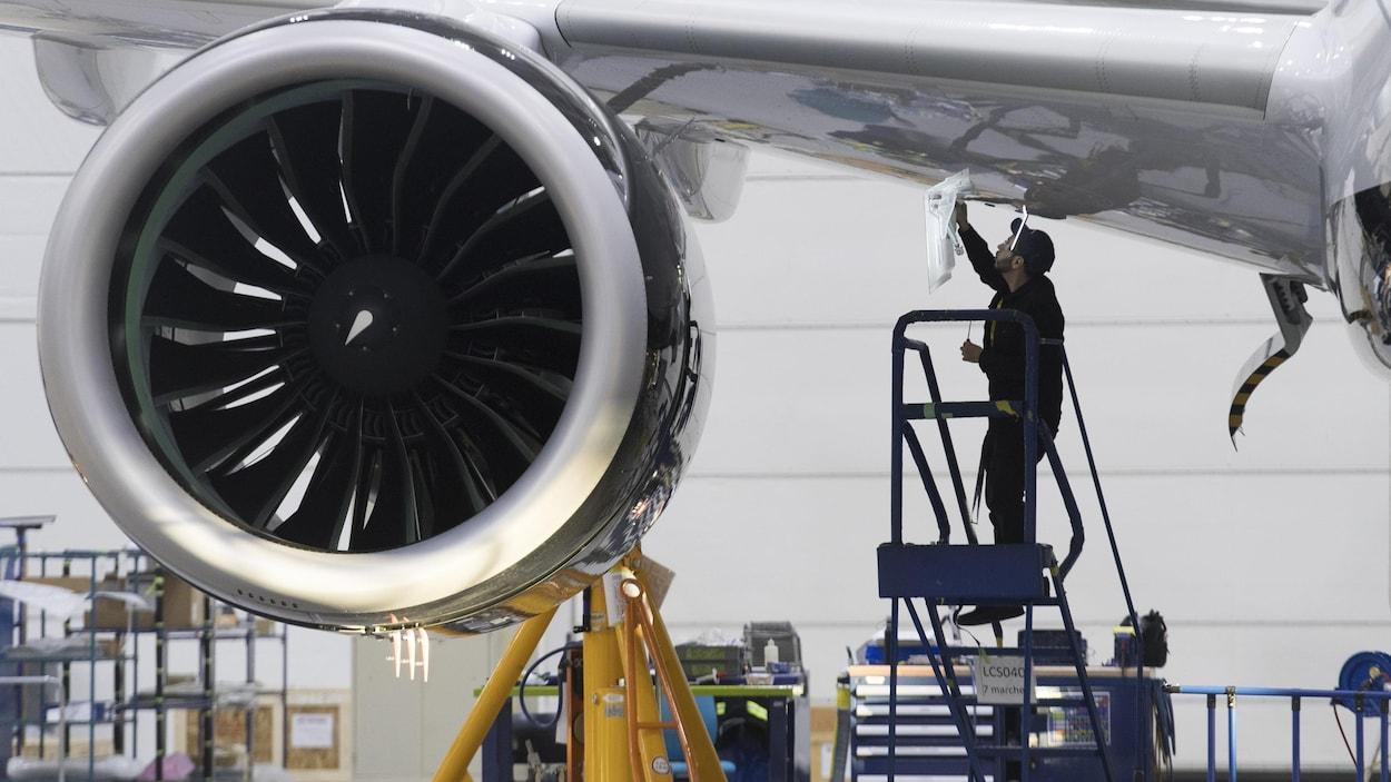 Un employé travaille sous l'aile d'un appareil.