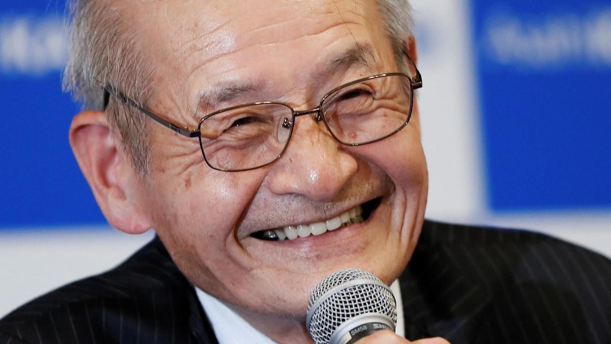 Akira Yoshino, tout sourire, au micro.