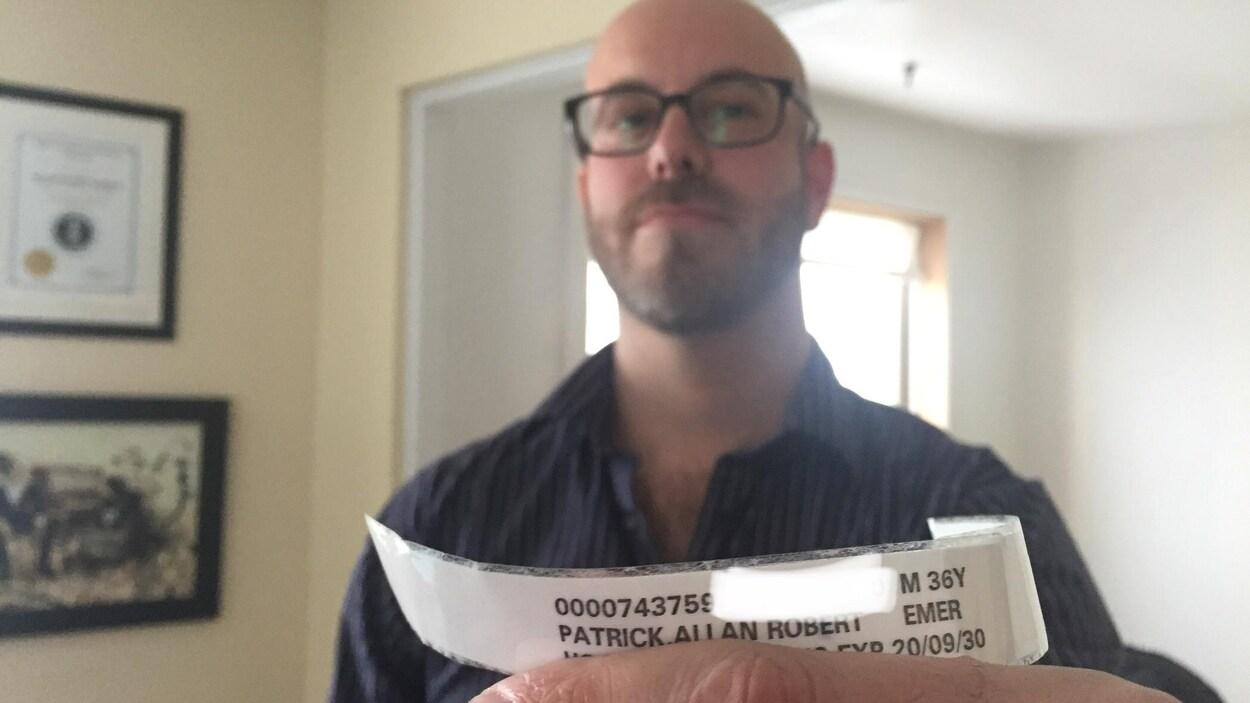 Un homme montre à la caméra un bracelet d'hôpital portant son nom.