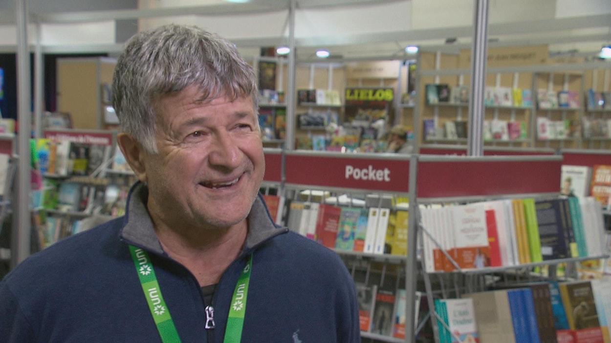 Alain Roberge en entrevue devant des étalages de livres.