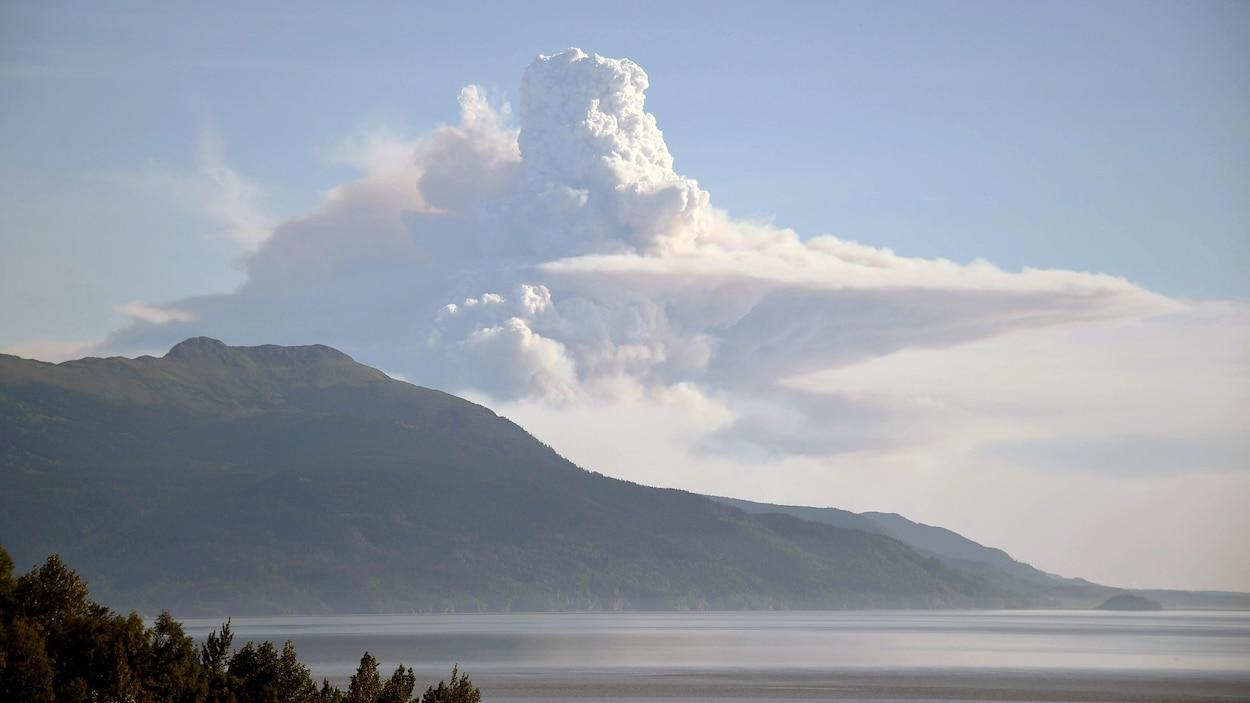 Un immense nuage de fumée s'élève derrière une montagne.