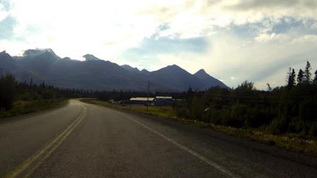 L'autoroute de l'Alaska rejoint l'horizon, au coeur d'un paysage nordique et montagneux.