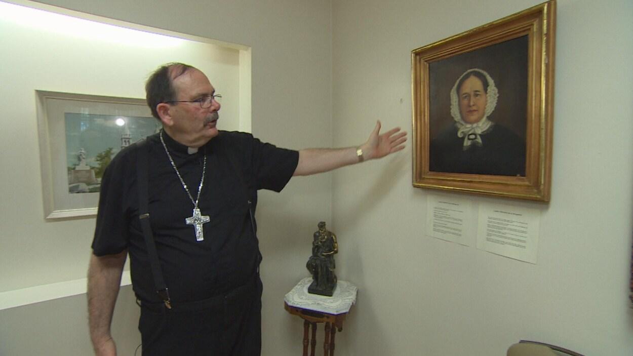 Un archevêque portant une croix autour du cou montre le tableau d'une femme de la main.