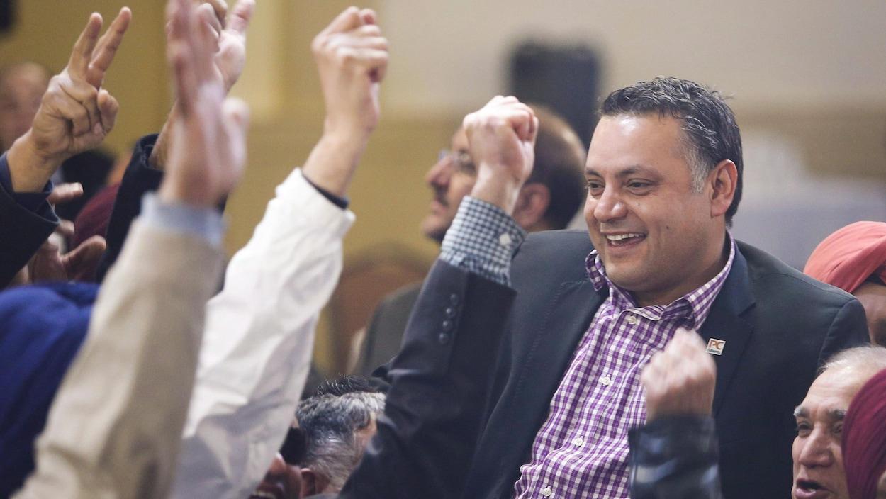 Un homme souriant dans une foule aux bras tendus en signe de victoire.