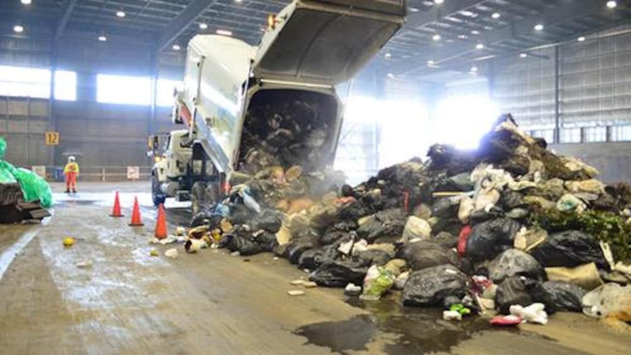 Un camion-benne déverse des sacs de déchets dans un hangar.