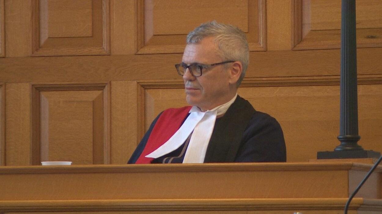 Un juge vêtu d'une toge assis en salle d'audience