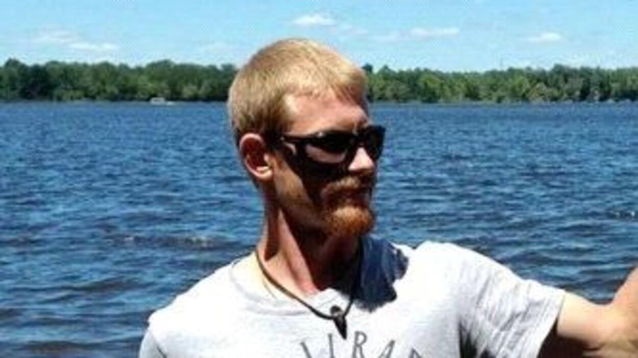 Un homme avec des lunettes de soleil pose pour une photo près d,june rivière en été.