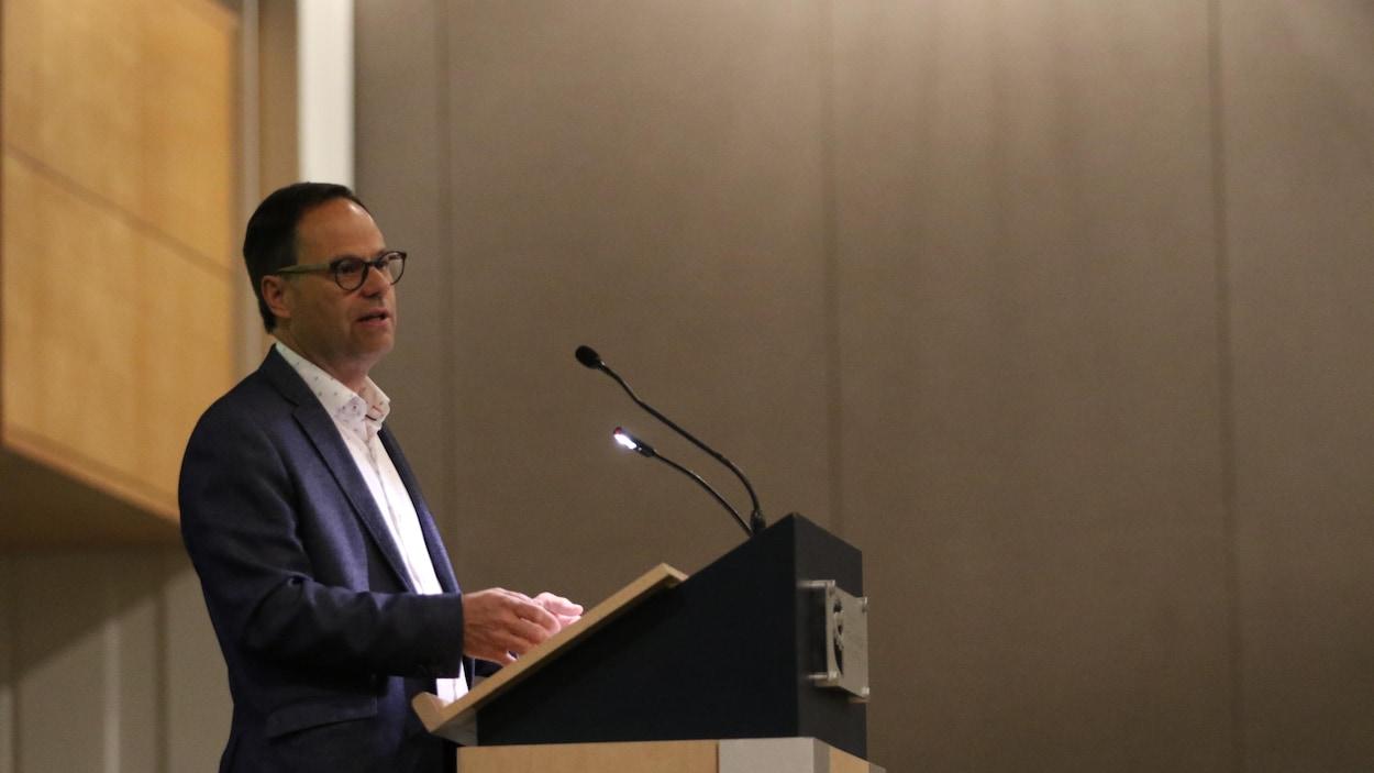 Alexandre Cusson parle au micro fixé sur un lutrin.