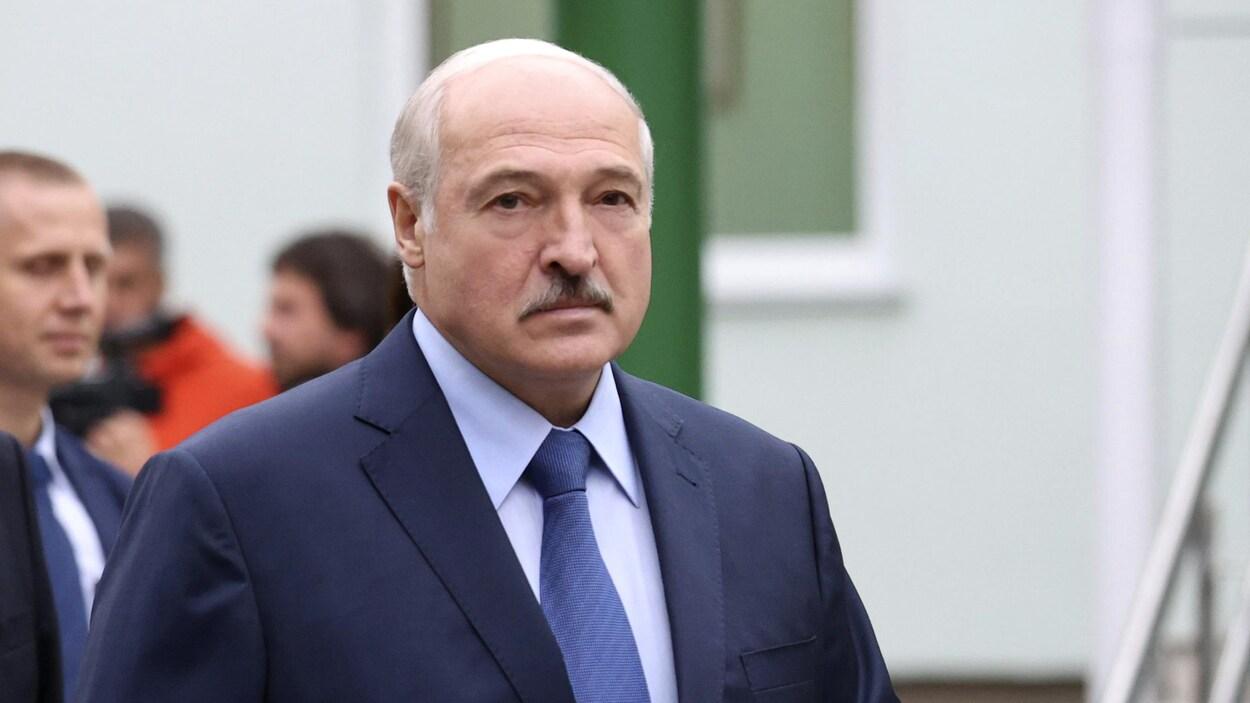 Alexandre Loukachenko marche dehors entouré de gens.