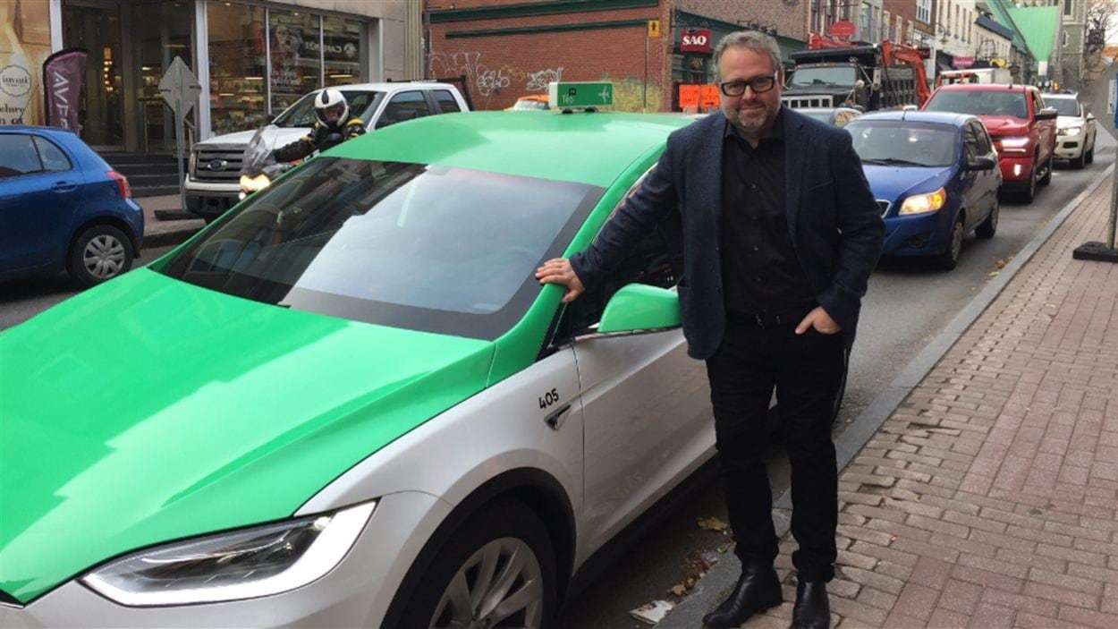 Le propriétaire de Téo Taxi, Alexandre Taillfer, prend la pose devant une voiture de la flotte.