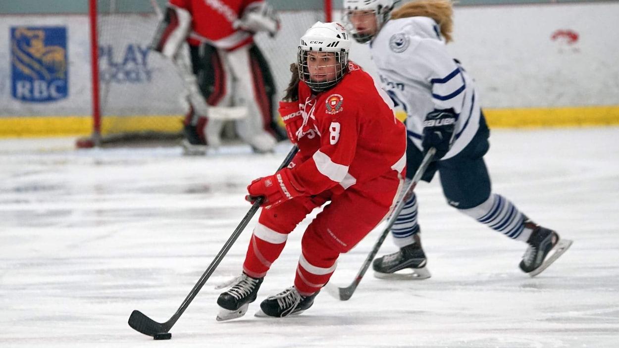 La Magogoise Alexie Guay joue également pour  les Spartans de Stanstead. On la voit ici arborer l'habit rouge des Spartans, en pleine action sur la glace.