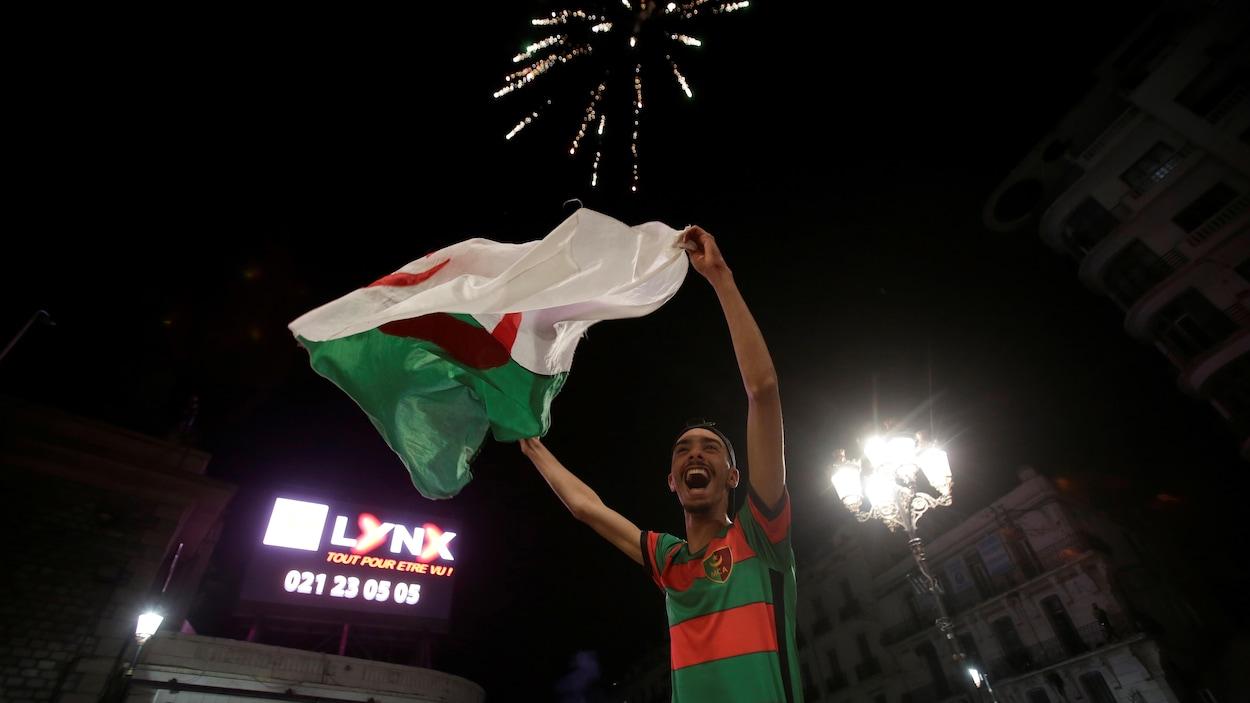 Un homme manifeste sa joie à Alger après l'annonce du président Abdelaziz Bouteflika qui a dit renoncer à se présenter pas pour un cinquième mandat.