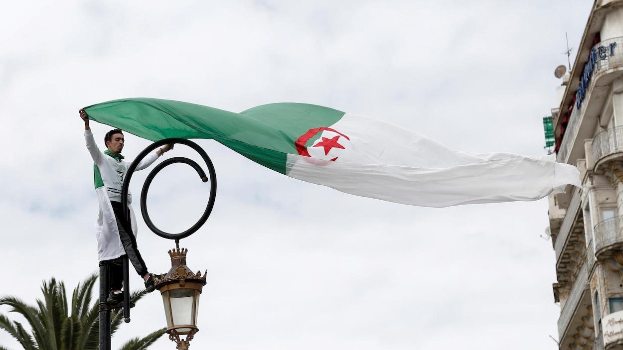 Un manifestant brandit le drapeau national algérien lors d'une manifestation à Alger.