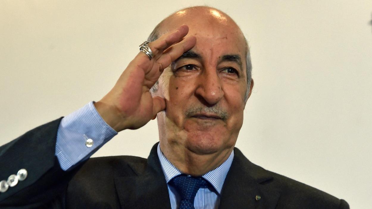 Le visage d'un homme en veston et cravate qui salue d'une main