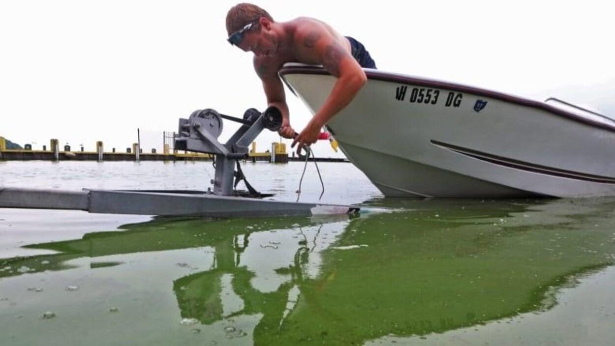 Un homme attache son bateau au-dessus d'une verte à cause des algues.