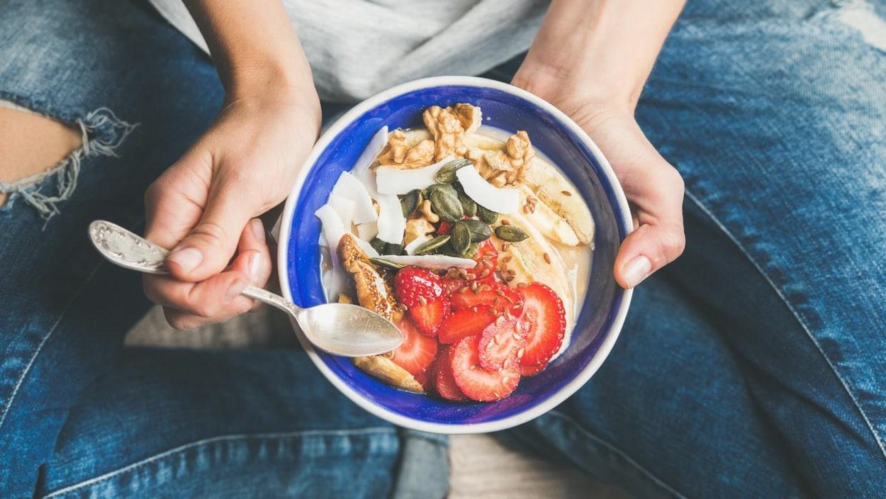 Une femme assise en tailleur tient entre ses mains un bol rempli de yaourt, fraises, graines et noix.