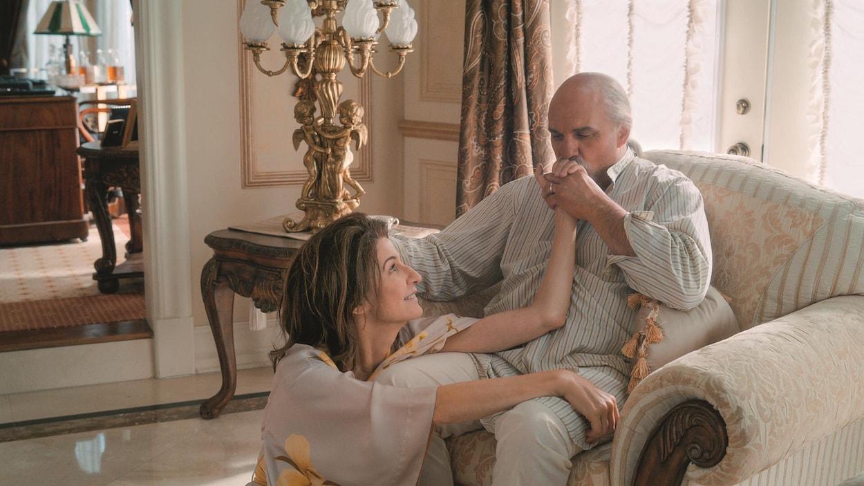 La femme est assise devant l'homme qui lui fait un baiser sur la main.