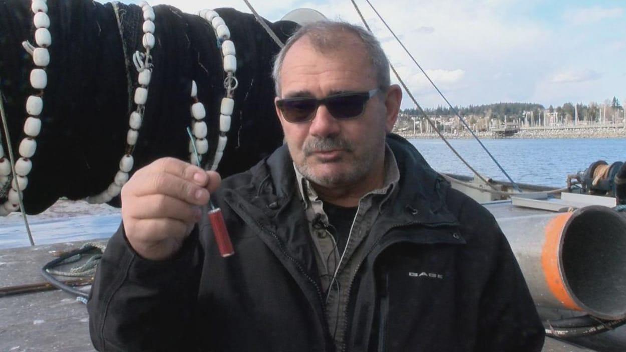Le pêcheur se tient sur le pont de son bateau et montre un pétard de la longueur d'un doigt.