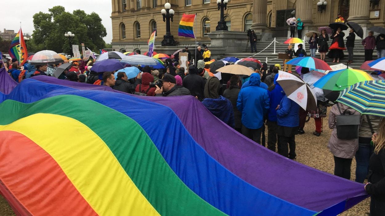 Des gens sont réunis tenant des drapeaux arc-en-ciel