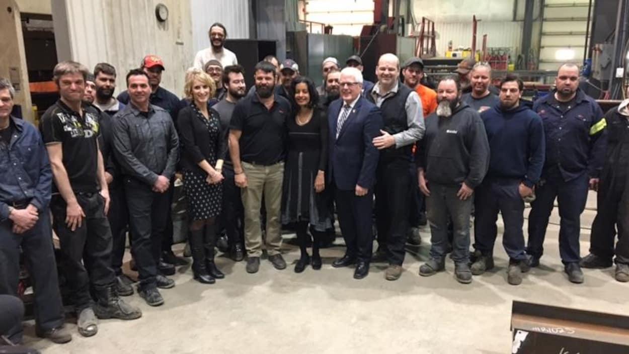 La ministre de l'Économie, Dominique Anglade, et le député de Dubuc, Serge Simard, entourés des dirigeants et travailleurs de l'usine Alma Soudure de Saint-Bruno