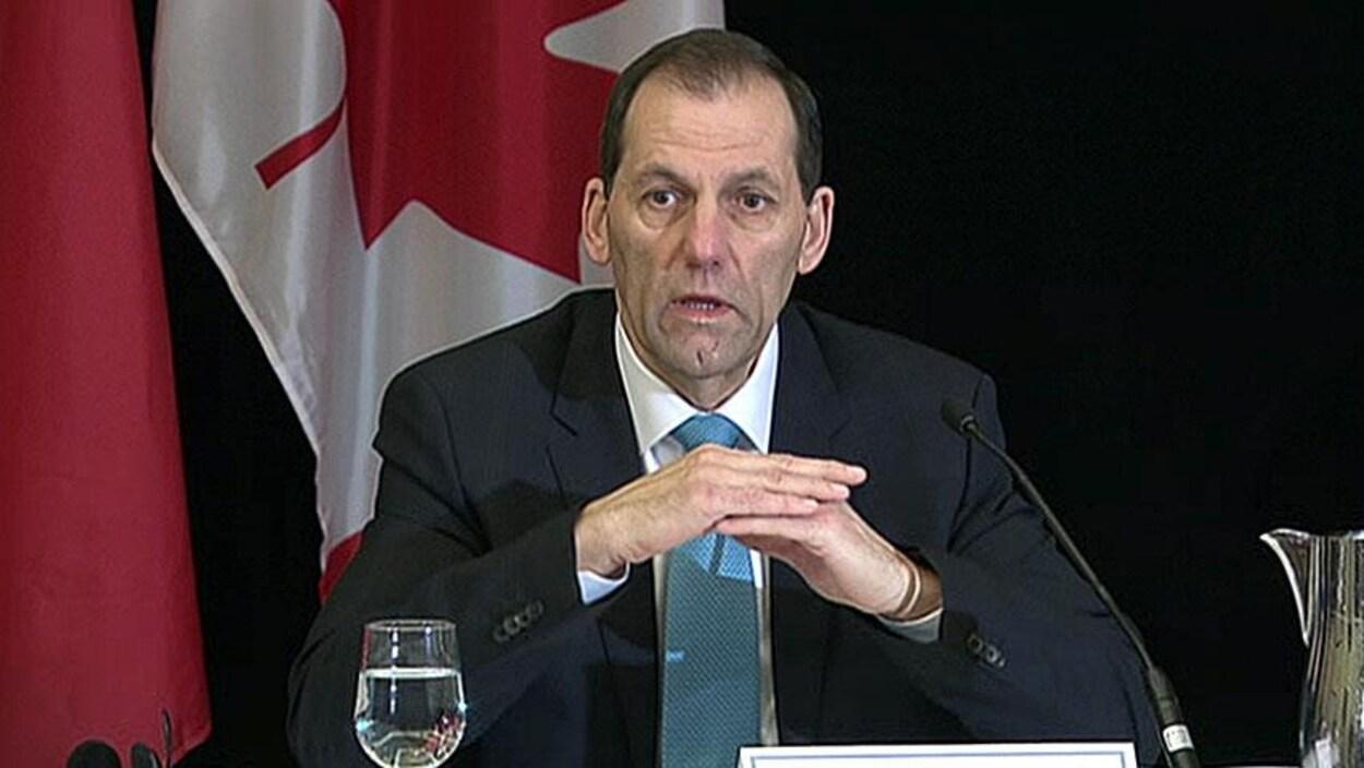 Un homme enu conférence de presse avec un drapeau du Canada à l'arrière-plan